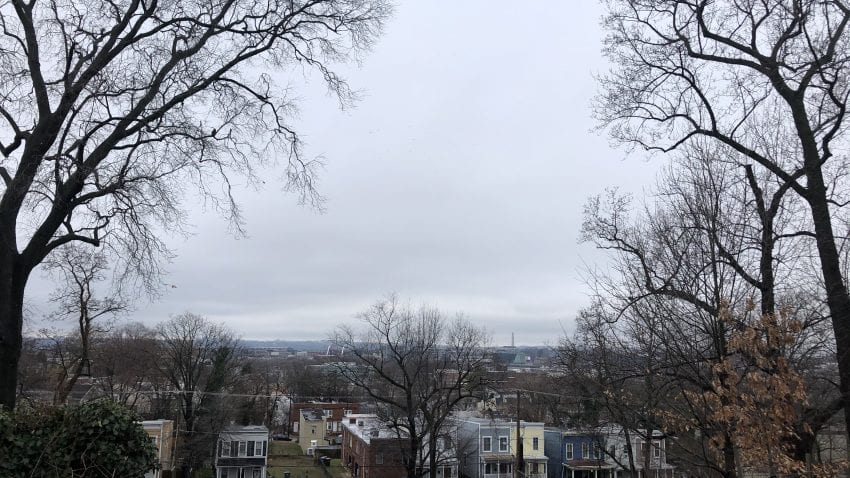 The view from Frederick Douglass' front yard in Anacostia. The Washington Monument can be seen in the distance, with trees and the top of houses closer to the front of the image.