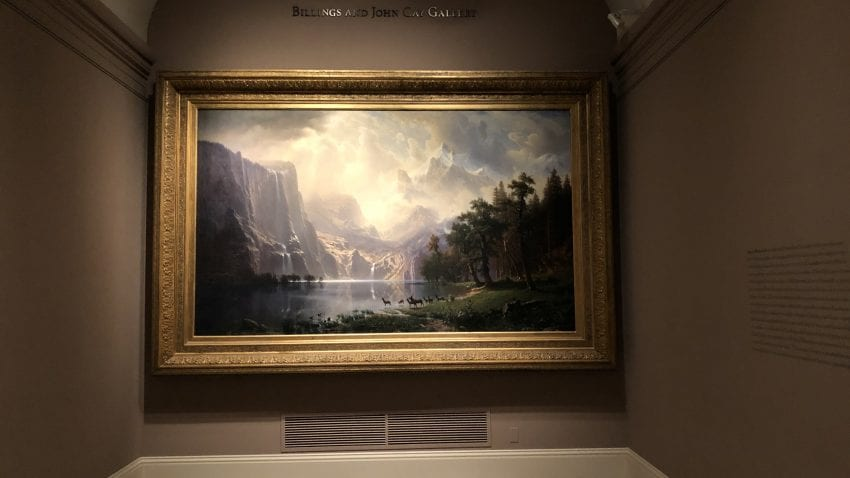 A painting of a mountainous landscape hangs in a corner of the Smithsonian American Art Museum. A light shines onto the painting.