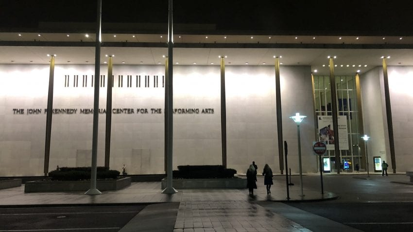 """A marble building with the words """"The John F. Kennedy Memorial Center for the Performing Arts."""" Gold pillars line up across the building and people walk into the large glass entrance."""