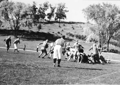 Football game beneath Thorson Hill which has many small pine trees.
