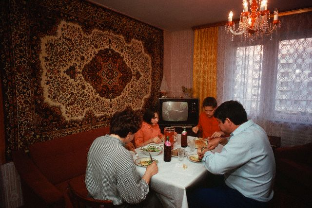 ca. May 1987, Moscow, USSR --- A well-to-do Soviet family eats dinner in their relatively luxurious Moscow apartment. They are among the few in the city who have a new, modern apartment and elegant furnishings. --- Image by © Wally McNamee/CORBIS