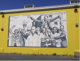 Photo of protest march mural on side of yellow building.